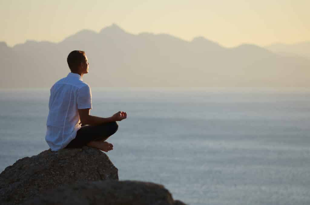 the-modern-gentleman-guy-sitting-on-a-rock-in-the-lotus-position