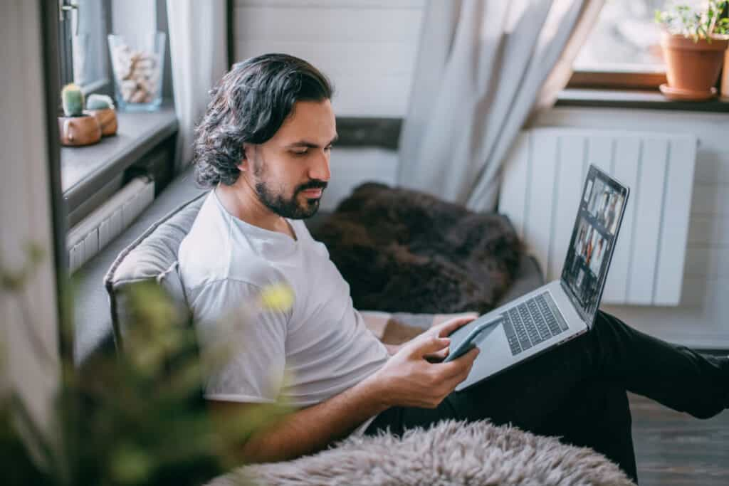 the-modern-gentleman-workplace-at-home-a-man-works-on-a-laptop-at-home-sits-on-a-sofa-in-the-living-room-during-the-day-talks-on-the-phone-work-from-home.